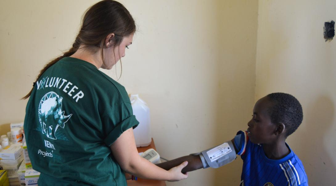 A teenage volunteer doing a medical internship with Projects Abroad in Kenya takes the blood pressure to a child.